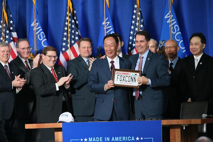 On November 10, 2017, Gov. Scott Walker and Foxconn Chairman Terry Gou signed the contract between the State of Wisconsin and Foxconn at SC Johnson in Racine.  Among other state, local and national government and Foxconn officials there, were Fisk Johnson, Chairman and CEO of SC Johnson who hosted the event, Speaker of the House, congressman Paul Ryan, Gov. Scott Walker, and Chairman of Foxconn Terry Gou. Terry Gou, Chairman of Foxconn (left) gets a custom Wisconsin auto license plate presented to him by Gov. Scott Walker.