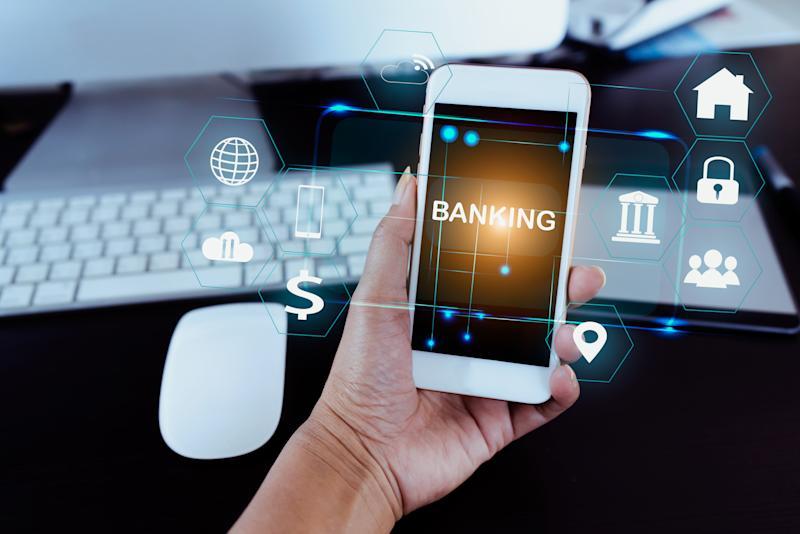 Businessman holding smart phone use word banking in hand with icon network connection on virtual screen dark background