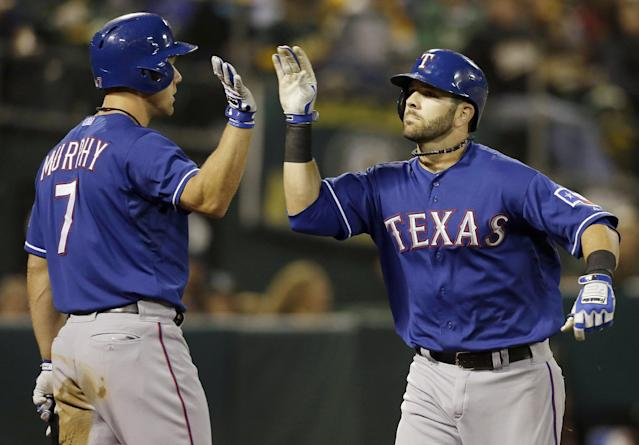 Texas Rangers' Mitch Moreland, right, celebrates with David Murphy (7) after hitting a solo home run off of Oakland Athletics pitcher Bartolo Colon in the fourth inning of a baseball game in Oakland, Calif., Tuesday, Sept. 3, 2013. (AP Photo/Jeff Chiu)