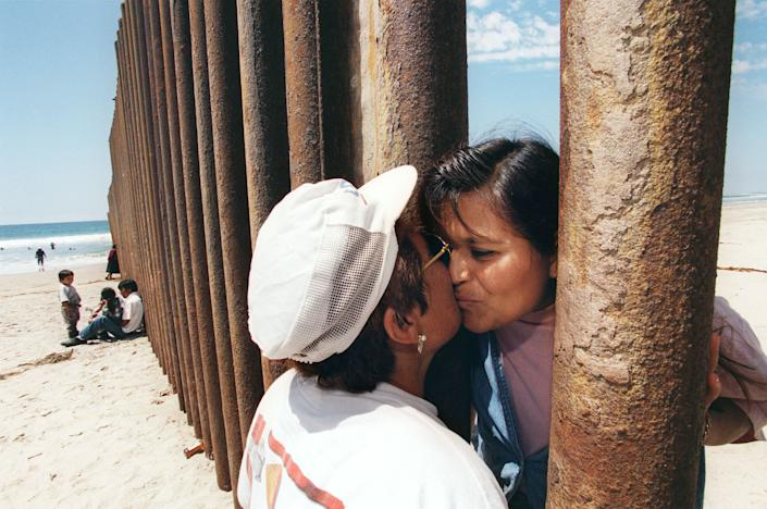 Esther Pereyra Rubalcaba (left) kisses her daughter Patricia through the wall separating the US and Min Tijuana, Mexico.