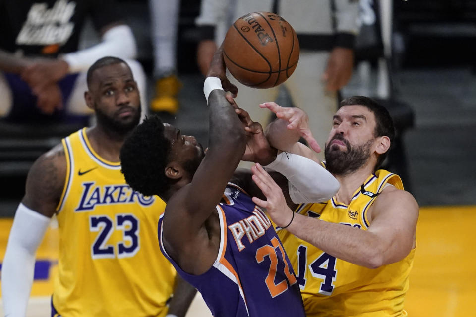 Phoenix Suns center Deandre Ayton (22) defends against Los Angeles Lakers center Marc Gasol (14) during the third quarter of Game 6 of an NBA basketball first-round playoff series Thursday, June 3, 2021, in Los Angeles. Los Angeles Lakers forward LeBron James (23) is at left. (AP Photo/Ashley Landis)