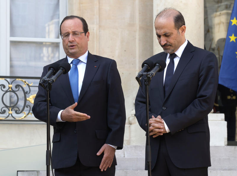 FILE - In this August 29, 2013, file photo, France's President Francois Hollande, left, and head of the Syrian National Coalition, Ahmad al-Jarba, right, talk to the media at the end of their meeting at the Elysee Palace, Paris, France. Syria's government and opposition will hold their first peace talks on Jan. 22 in Geneva, in an attempt to halt the nearly 3-year-old civil war that has killed more than 100,000 people, the United Nations announces. (AP Photo/Michel Euler, File)