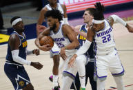 Sacramento Kings forward Marvin Bagley III, second from left, pulls in a rebound as Denver Nuggets forward Paul Millsap, left, and center Nikola Jokic, second from right, defend, near Sacramento center Richaun Holmes, right, during the first half of an NBA basketball game Wednesday, Dec. 23, 2020, in Denver. (AP Photo/David Zalubowski)