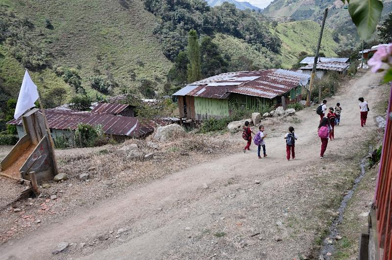 Children walk along a street near a white flag on August 26, 2016, in San Miguel, Tolima department, Colombia, one of the 22 areas where FARC former rebels will be relocated after the signing of a peace accord (AFP Photo/Guillermo Legaria)