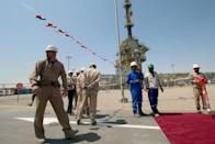 FILE PHOTO: A member of security foreign personnel stays guard next to Exxon's foreign staff and Iraqi staff of the West Qurna-1 oilfield, which is operated by ExxonMobil, during the opening ceremony near Basra