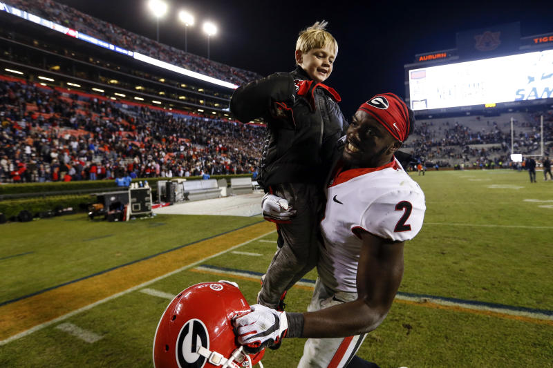 Georgia defensive back Richard LeCounte (2) holds up Andrew Smart, son of Kirby Smart, after the team defeated Auburn 21-14 in an NCAA college football game, Saturday, Nov. 16, 2019, in Auburn, Ala. (AP Photo/Butch Dill)