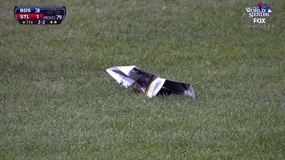 Jon Lester gently hands giant paper airplane to batboy during Yadier Molina at-bat