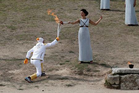 Olympics - Dress Rehearsal - Lighting Ceremony of the Olympic Flame Pyeongchang 2018 - Ancient Olympia, Olympia, Greece - October 23, 2017 Greek actress Katerina Lehou, playing the role of High Priestess, passes the flame to the first torchbearer, Greek cross country skiing athlete Apostolos Aggelis, during the dress rehearsal for the Olympic flame lighting ceremony for the Pyeongchang 2018 Winter Olympic Games at the site of ancient Olympia in Greece REUTERS/Costas Baltas