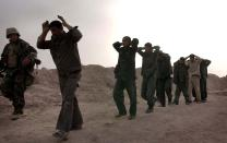 FILE - In this March 21, 2003, file photo, Iraqi soldiers surrender to U.S. Marines with India Co., 3rd Battalion, 7th Marines, 1st Marine Division following a gunfight at the headquarters of the Iraqi 51st and 32nd mechanized infantry divisions near Az Bayer, Iraq. The U.S. launched its invasion of Iraq on March 20, 2003, unleashing a war that led to an insurgency, sectarian violence and tens of thousands of deaths. (AP Photo/Laura Rauch, File)