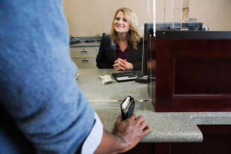 A female bank teller smiles at a male customer with his wallet in hand.