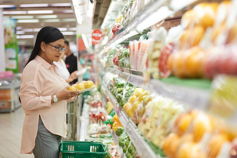 A woman standing in the produce aisle at a grocery store.