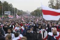 People with old Belarusian national flags march during an opposition rally to protest the official presidential election results in Minsk, Belarus, Sunday, Sept. 27, 2020. Hundreds of thousands of Belarusians have been protesting daily since the Aug. 9 presidential election. (AP Photo/TUT.by)
