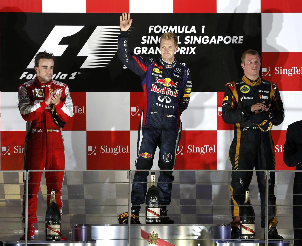 Red Bull Formula One driver Sebastian Vettel of Germany (C), Ferrari Formula One driver Fernando Alonso of Spain (L) and Lotus F1 Formula One driver Kimi Raikkonen of Finland (R) stand on the podium after the Singapore F1 Grand Prix at the Marina Bay street circuit in Singapore September 22, 2013. Vettel cruised to a third straight Singapore Grand Prix victory on Sunday and moved closer to a fourth consecutive Formula One world title with a dominant drive under the floodlights at the Marina Bay Street Circuit. REUTERS/Edgar Su (SINGAPORE - Tags: SPORT MOTORSPORT F1)