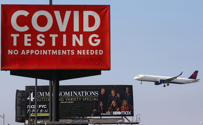 A Delta Air Lines plane lands near a COVID-19 testing sign at Los Angeles International Airport (LAX) on August 25, 2021.