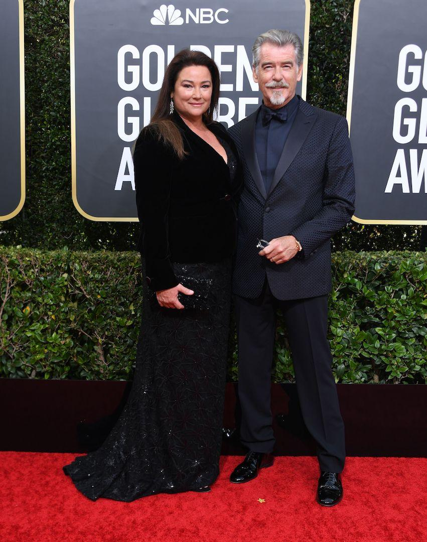 Pierce Brosnan chose a navy tuxedo for the ceremony while his wife, Keely Shaye Smith opted for a sweeping black sequin gown. <em>[Photo: Getty]</em>