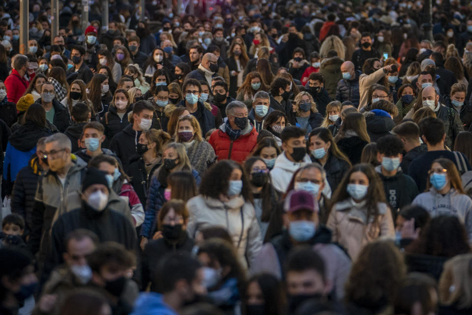 "People wearing face masks to protect against the spread of coronavirus walk along a busy street in downtown Barcelona, Spain, Monday, Dec. 7, 2020. The Spanish government is pleading with people to voluntarily observe social distancing rules and other measures over the Christmas holiday, with the health minister saying ""we can't put a police officer in every house."" (AP Photo/Emilio Morenatti)"