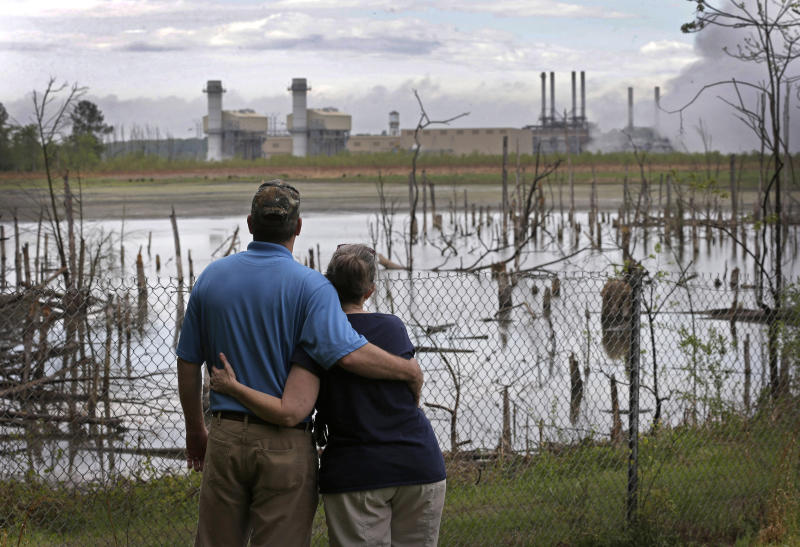 FILE - In this April 25, 2014, file photo, Bryant Gobble, left, embraces his wife, Sherry Gobble, right, as they look from their yard across an ash pond full of dead trees toward Duke Energy's Buck Steam Station in Dukeville, N.C. The federal, North Carolina and Virginia governments want a judge to declare Charlotte-based Duke Energy liable for environmental damage from a leak five years ago that left miles of a river shared by the two states coated in hazardous coal ash. Government lawyers on Thursday, July 18, 2019 sought to have Duke Energy declared responsible for harming fish, birds, amphibians and the bottom of the Dan River.  (AP Photo/Chuck Burton, File)