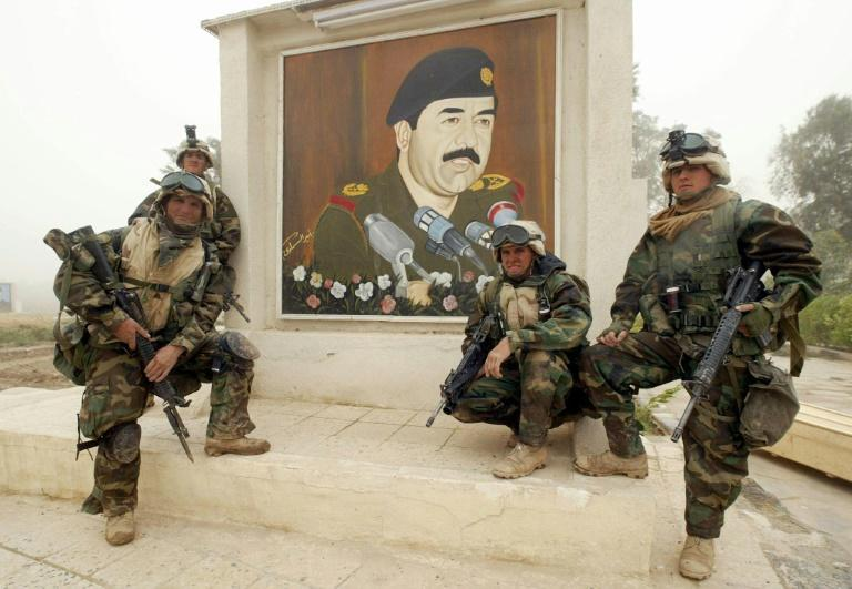 Marines from the 2nd Battalion, 8th Regiment pose next to a mural of Iraqi president Saddam Hussein found after taking control of a hospital allegedly used for military purposes by Iraqi forces near the Iraqi city of Nasiriyah in March 2003