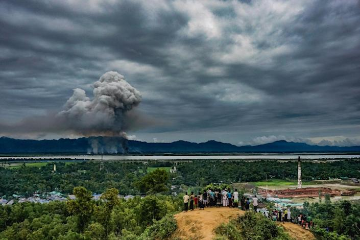 <p>Watch houses burn: A group of Rohingya at the Leda makeshift settlement in Cox's Bazar, Bangladesh, watch as houses burn just across the border in Myanmar, Sept. 9, 2017.<br>After militants of the Arakan Rohingya Salvation Army (ARSA) launched an assault on a Myanmar government police post in August, Rohingya villages were targeted and houses burned, causing an exodus of refugees to Bangladesh. The Myanmar government blamed ARSA for the village attacks. According to the refugees themselves and Human Rights Watch, which analyzed satellite imagery, Myanmar security forces set the fires. By the end of November more than 350 villages had been partially or completely destroyed. (Photo: Md Masfiqur Akhtar Sohan/NurPhoto Agency) </p>
