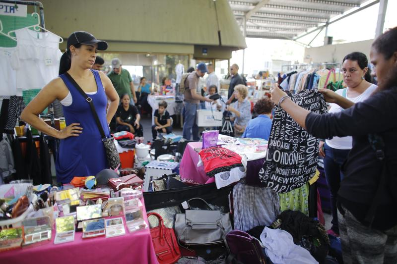 In this Nov. 3, 2019 photo, Yenika Calderon, left, watches customers look through her personal belongings at a secondhand market, in Caracas, Venezuela. Calderon, 41, who is hoping to pocket enough money to give her young family a fresh start far away in Spain, has trekked to the secondhand market every Sunday in recent weeks, haggling with customers over prices for her favorite handbags and her son's baby clothes. (AP Photo/Ariana Cubillos)