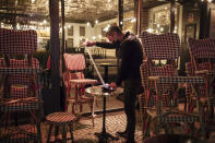 FILE - In this Oct. 17, 2020 file photo, a waiter checks the final revenue as he closes a bar terrace in Paris. The coronavirus pandemic is gathering strength again in Europe and, with winter coming, its restaurant industry is struggling. The spring lockdowns were already devastating for many, and now a new set restrictions is dealing a second blow. Some governments have ordered restaurants closed; others have imposed restrictions curtailing how they operate. (AP Photo/Lewis Joly, File)