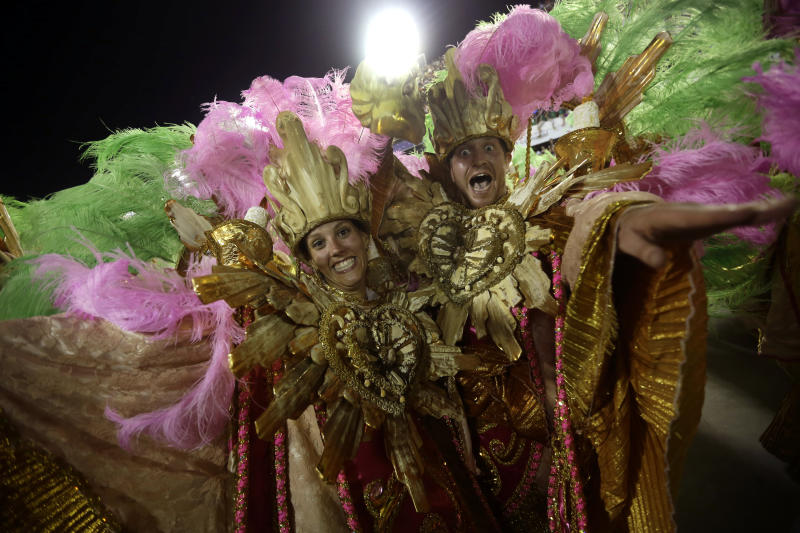 """U.S. citizen Paul Leaury, right, and an unidentified fellow foreign member of the Mangueira samba school, dance during a carnival parade at the Sambadrome in Rio de Janeiro, Brazil, Tuesday, Feb. 12, 2013. While non-Brazilians have long shelled out hundreds of dollars for the right to dress up in over-the-top costumes and boogie in Rio's samba school parades, which wrapped up Monday in an all-night extravaganza, few in the so-called """"alas dos gringos,"""" or """"foreigners' wings,"""" know how to dance the samba well, bopping along goofily in the parades and waving at the crowds of spectators. (AP Photo/Silvia Izquierdo)"""