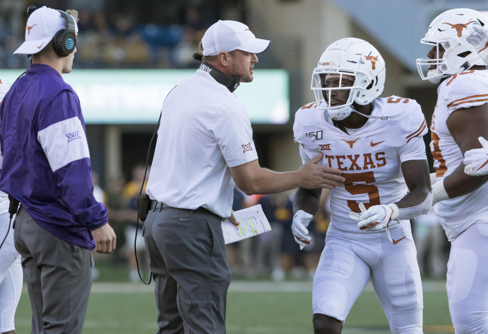 Texas head coach Tom Herman talks to defensive back D'Shawn Jamison (5) during the second half of an NCAA college football game against West Virginia, Saturday, Oct. 5, 2019, in Morgantown, W.Va. (AP Photo/Raymond Thompson)