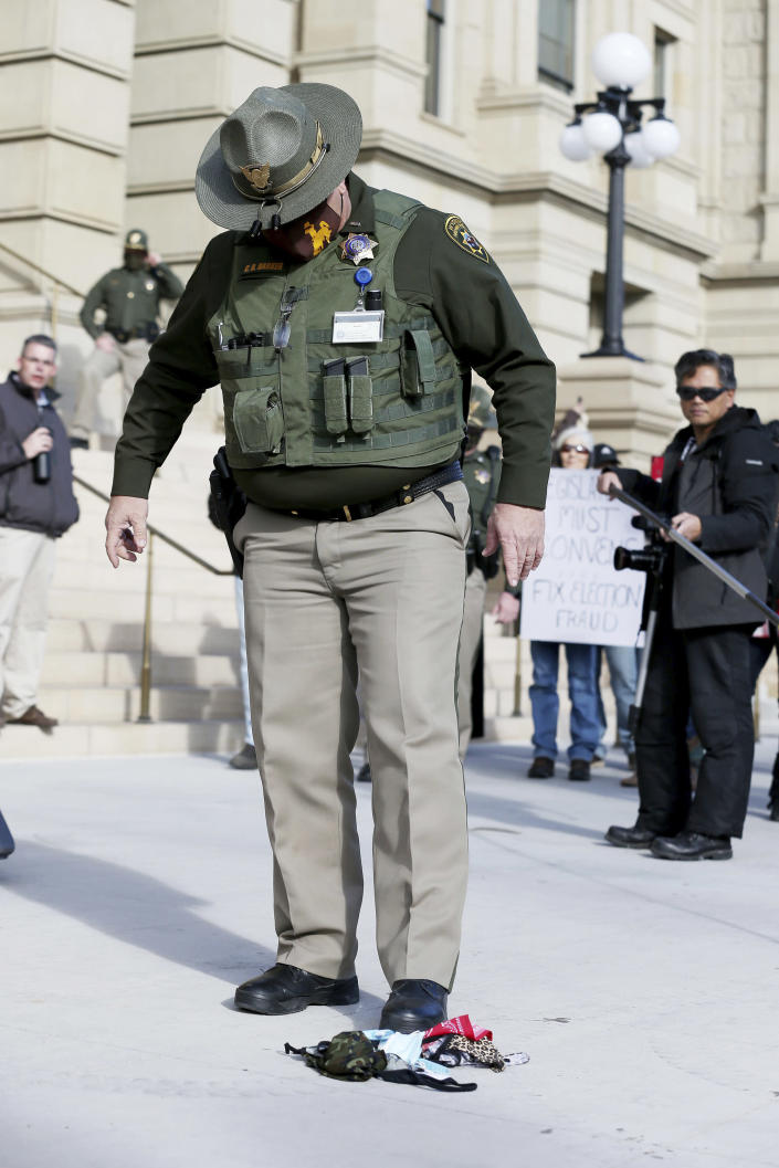 In this Monday, Jan. 4, 2021, photo a Wyoming State Trooper stomps out a pile of burning masks during the Free Wyoming rally against Wyoming Gov. Mark Gordon and the face mask mandates outside the Capitol in downtown Cheyenne, Wyo. Gov. Gordon quietly mobilized dozens of National Guard troops in case of any violence at the state Capitol in Cheyenne, in January. The deployment came to light Friday, March 5, 2021, after an Associated Press inquiry after the Jan. 6 riot at the U.S. Capitol, which left five dead. (Michael Cummo/The Wyoming Tribune Eagle via AP)