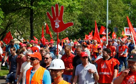 FILE PHOTO: A worker has a sign on helmet with text 'We are for 5%' as steel workers of Germany's IG Metall union protest for higher wages in Cologne