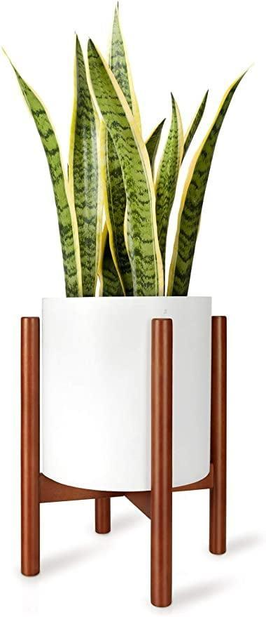 """<p>If you already have a simple pot and are looking for a stand, get this popular <a href=""""https://www.popsugar.com/buy/Mkono-Plant-Stand-Mid-Century-Pot-Holder-581170?p_name=Mkono%20Plant%20Stand%20Mid%20Century%20Pot%20Holder&retailer=amazon.com&pid=581170&price=27&evar1=casa%3Aus&evar9=45784601&evar98=https%3A%2F%2Fwww.popsugar.com%2Fhome%2Fphoto-gallery%2F45784601%2Fimage%2F47575653%2FMkono-Plant-Stand-Mid-Century-Pot-Holder&list1=shopping%2Cproducts%20under%20%2450%2Cdecor%20inspiration%2Caffordable%20shopping%2Chome%20shopping&prop13=api&pdata=1"""" class=""""link rapid-noclick-resp"""" rel=""""nofollow noopener"""" target=""""_blank"""" data-ylk=""""slk:Mkono Plant Stand Mid Century Pot Holder"""">Mkono Plant Stand Mid Century Pot Holder</a> ($27).</p>"""