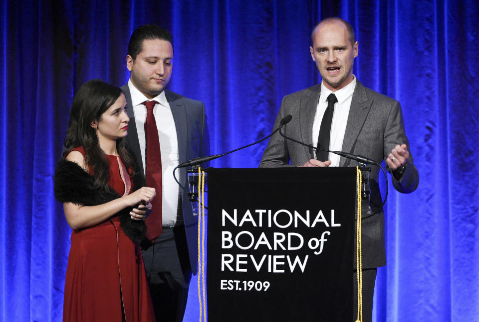 """Waad al-Kateab, left, Hamza al-Kateab and Edward Watts accept the National Board of Review freedom of expression award for """"For Sama"""". (Photo by Evan Agostini/Invision/AP)"""
