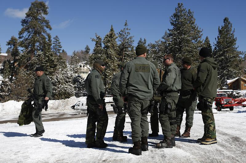 San Bernardino County Sheriff's deputies gather at the command post in Big Bear Lake, Calif, Saturday, Feb. 9, 2013.  Clear skies allowed aircraft with heat-sensing technology to aid scores of officers searching in the snow-covered San Bernardino Mountains for Christopher Dorner, the former Los Angeles police officer suspected of killing three people in a vengeance-fueled rampage aimed at those he blames for ending his career. (AP Photo/Jae C. Hong)