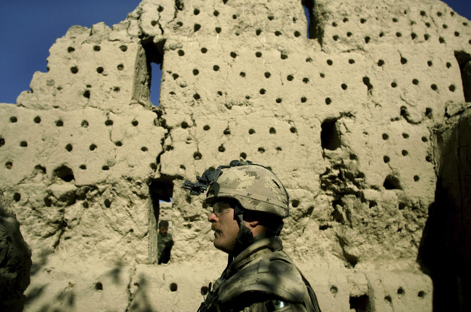 FILE - In this Nov. 22, 2006 file photo, a Canadian soldier, and a soldier from the Afghan National Army, behind wall, walk along a destroyed grape drying silo at the Canadian base near the town of Zhari in the Kandahar province of Afghanistan. The holes in the wall are for mounting sticks for drying grapes. (AP Photo/David Guttenfelder, File)