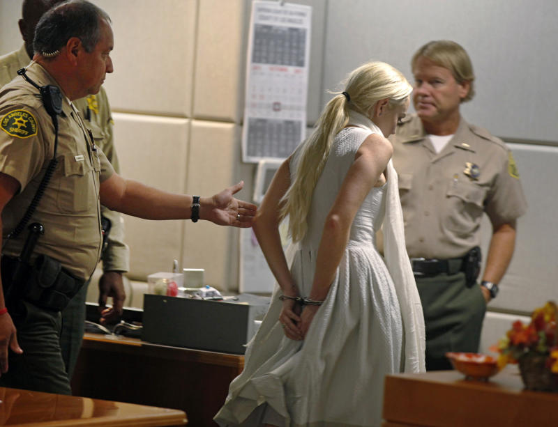 Lindsay Lohan is taken into custody by Los Angeles Country sheriffs after a judge finds her in violation of probation Wednesday, Oct. 19, 2011, in Los Angeles. Superior Court Judge Stephanie Sautner revoked Lohan's probation Wednesday after the actress encountered problems during her community service assignment at a women's shelter. Bail has been set at $100,000. (AP Photo/Mark Boster, Pool)