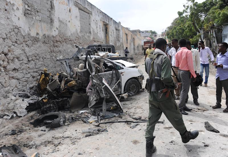 A soldier walks past the site of a major car bomb and gun attack against an intelligence headquarters and detention facility in the center of Mogadishu, August 31, 2014 (AFP Photo/Mohamed Abdiwahab)