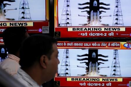 People watch a live broadcast of India's second lunar mission, Chandrayaan-2, inside an electronics showroom in Kolkata