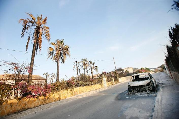 The charred remains of a car are seen in a residential area affected by forest fires near the Spanish resort of Javea, on September 5, 2016 (AFP Photo/Manuel Lorenzo)