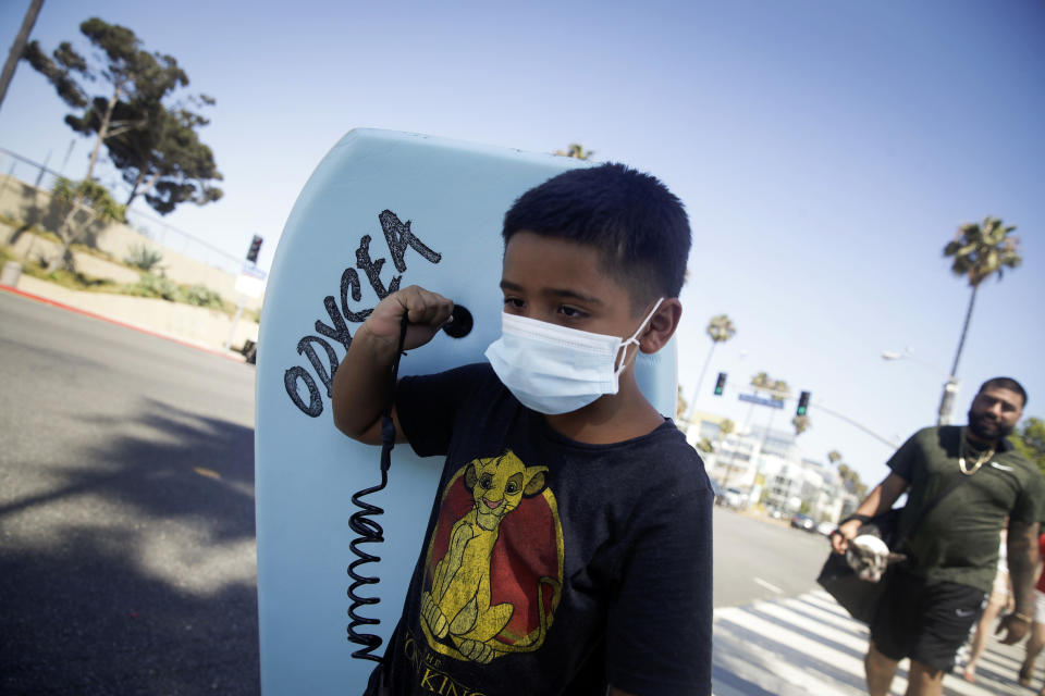 Elijah Cobos wear a face mask as he carries a boogie board to the beach Sunday, July 12, 2020, in Santa Monica, Calif., amid the coronavirus pandemic . A heat wave has brought crowds to California's beaches as the state grappled with a spike in coronavirus infections and hospitalizations. (AP Photo/Marcio Jose Sanchez)