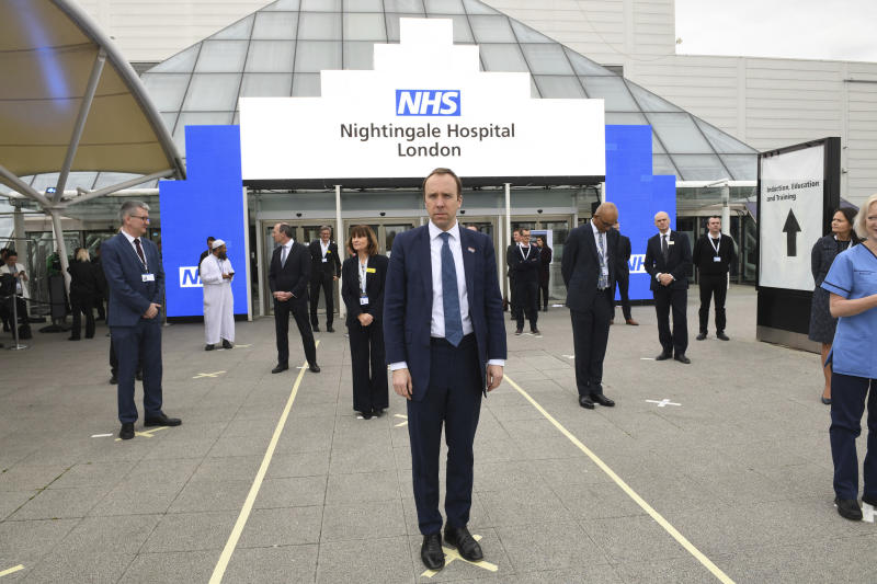 Britain's Health Secretary Matt Hancock and NHS staff stand on marks on the ground, put in place to ensure social distancing guidelines are adhered to, ahead of the opening of the NHS Nightingale Hospital at the ExCel centre in London, Friday April 3, 2020. The ExCel centre which has been converted into a 4000 bed temporary hospital NHS Nightingale amid the growing coronavirus outbreak. (Stefan Rousseau/Pool Photo via AP)