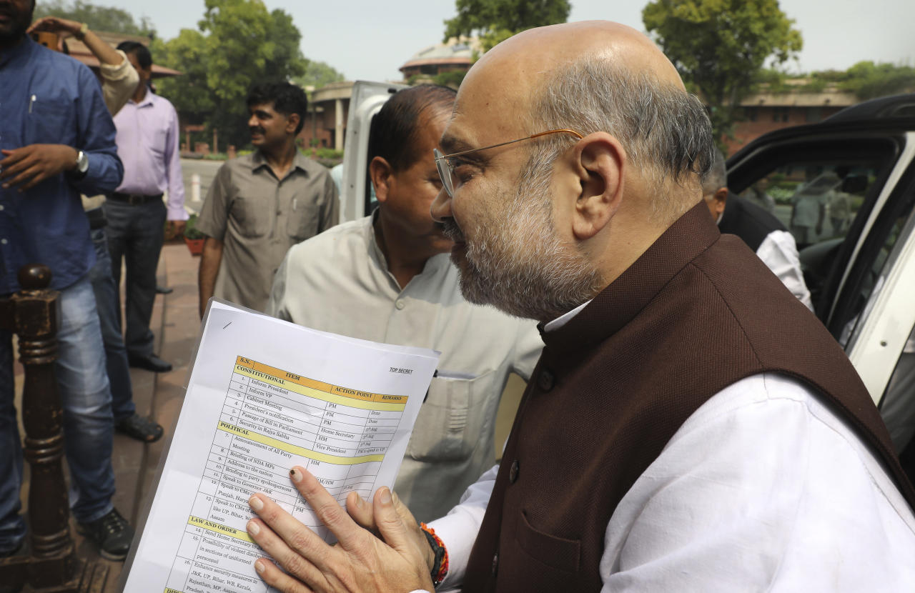 Indian Home Minister Amit Shah arrives at the Parliament carrying copy of a confidential document that lists out the procedure for revoking Kashmir's special status in New Delhi, India, Monday, Aug.5, 2019. India's government has revoked disputed Kashmir's special status with a presidential order as thousands of newly deployed troops arrived and some internet and phone services were cut in the restive Himalayan region where most people oppose Indian rule. (AP Photo/Manish Swarup)
