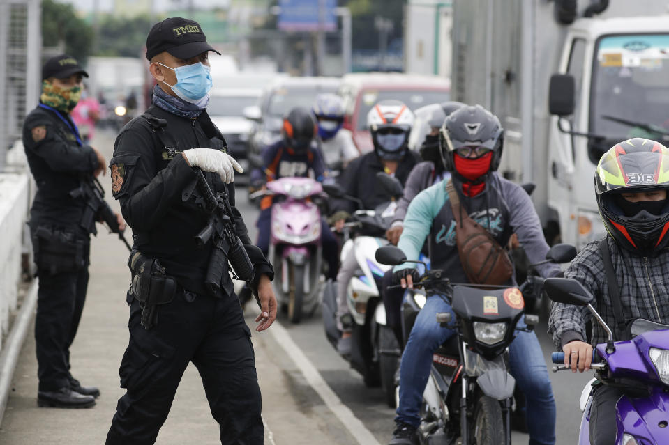 Police operate a checkpoint Tuesday, Aug. 4, 2020, outside Manila, Philippines, as the capital is placed on another lockdown in the hopes of controlling the surge of coronavirus cases. Commuter trains, buses and other public vehicles stayed off the main roads of the Philippine capital Tuesday and police were again staffing checkpoints to restrict public travel. (AP Photo/Aaron Favila)