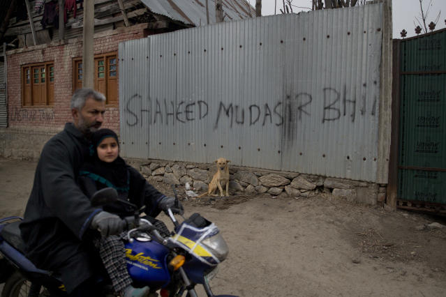 In this Dec. 26, 2018 photo, a Kashmiri man along with his daughter drives past a graffiti on the house of Mudassir Rashid Parray, referring to him as a martyr, in Hajin village, north of Srinagar, Indian controlled Kashmir. Mudassir, who was then 14-years-old, and another teenager walked away from a local soccer pitch in the Kashmiri town of Hajin on a hot day in August, only to return home months later in body bags. Dying with his teammate in an 18-hour firefight in December, Mudassir became the youngest militant slain fighting Indian troops in a three-decade insurgency in Kashmir. (AP Photo/Dar Yasin)