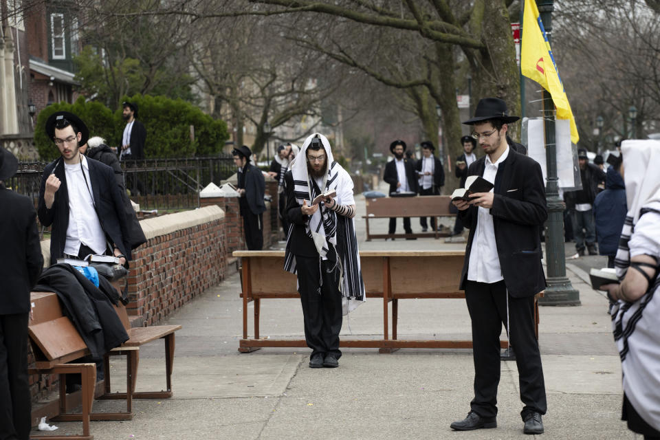 """Orthodox Jewish men use """"social distancing"""" as they pray outside the Chabad Lubavitch World Headquarters, Friday, March 20, 2020 in the Brooklyn borough of New York, before leaders of six major organizations in their faith released a joint statement urging worshippers to """"avoid, to the maximum extent feasible, any outside interactions"""" to help stop the coronavirus pandemic. Orthodox Jewish leaders mounted their show of unity to underscore to a wide swath of congregants the importance of behavioral changes that amount to a massive upheaval in their faith communities. (AP Photo/Mark Lennihan)"""