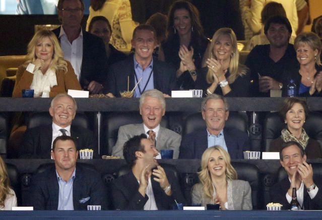 From center left, Dallas Cowboys owner Jerry Jones, former presidents Bill Clinton and George W. Bush and former first lady Laura Bush as well as Cowboys head coach Jason Garrett, second from top left, watch action between Connecticut and Kentucky during the first half of the NCAA Final Four tournament college basketball championship game Monday, April 7, 2014, in Arlington, Texas. (AP Photo/Tony Gutierrez)