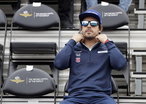 FILE - In this May 27, 2017, file photo, Fernando Alonso, of Spain, waits for the start of the drivers meeting for the Indianapolis 500 auto race at Indianapolis Motor Speedway, in Indianapolis. McLaren will put a car on track at Indianapolis Motor Speedway for the first time since 1976 when Fernando Alonso tests Wednesday. Alonso is trying to win motorsports version of the Triple Crown, while the famed manufacturer is considering a return to IndyCar competition. (AP Photo/Darron Cummings, File)