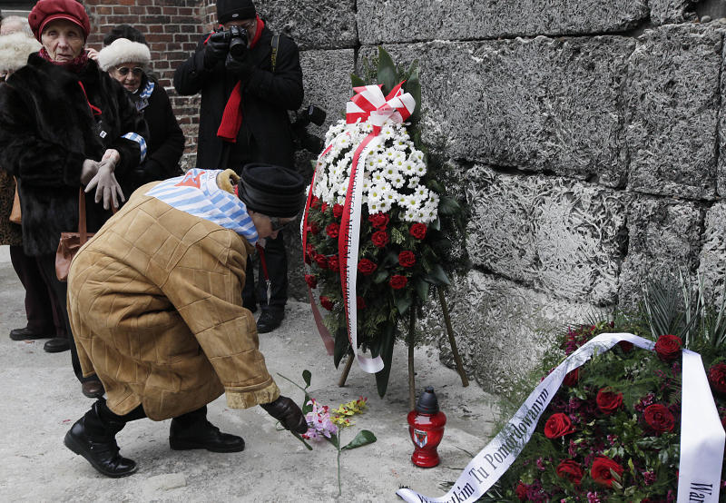 Auschwitz survivors lay a wreath and flowers at the former Nazi death camp's Executions wall in Oswiecim, Poland, on Monday, Jan. 27, 2014, to mark 69 years since the Soviet Red Army liberated the camp. Israeli lawmakers and government officials are to attend anniversary observances later in the day. The Nazis killed some 1.5 million people, mostly Jews at the camp during World War II.(AP Photo/Czarek Sokolowski)