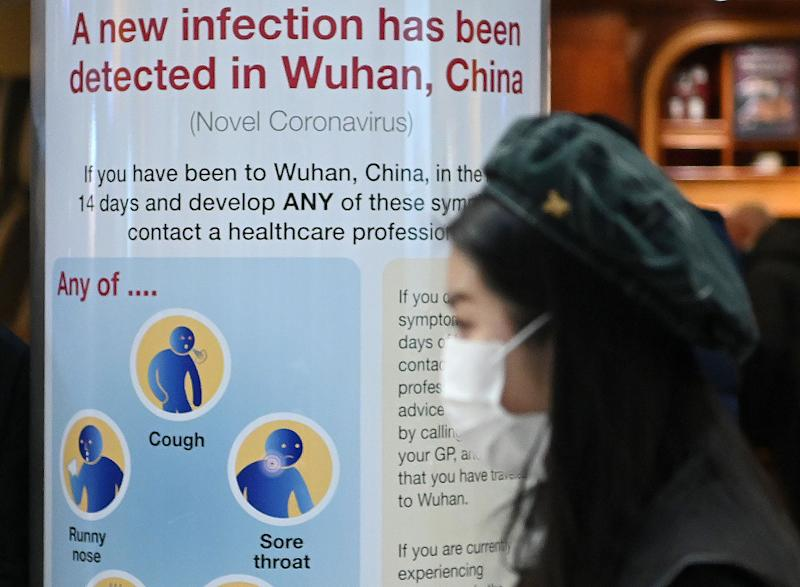 "A woman wearing a face mask passes a Public Health England sign, warning passengers arriving on flights into the UK, that a virus, Coronavirus, has been detected in Wuhan in China, at Terminal 4 of London Heathrow Airport in west London on January 28, 2020. - Chinese President Xi Jinping said Tuesday the country was waging a serious fight against the ""demon"" coronavirus outbreak and pledged transparency in the government's efforts to contain the disease. (Photo by DANIEL LEAL-OLIVAS / AFP) (Photo by DANIEL LEAL-OLIVAS/AFP via Getty Images)"