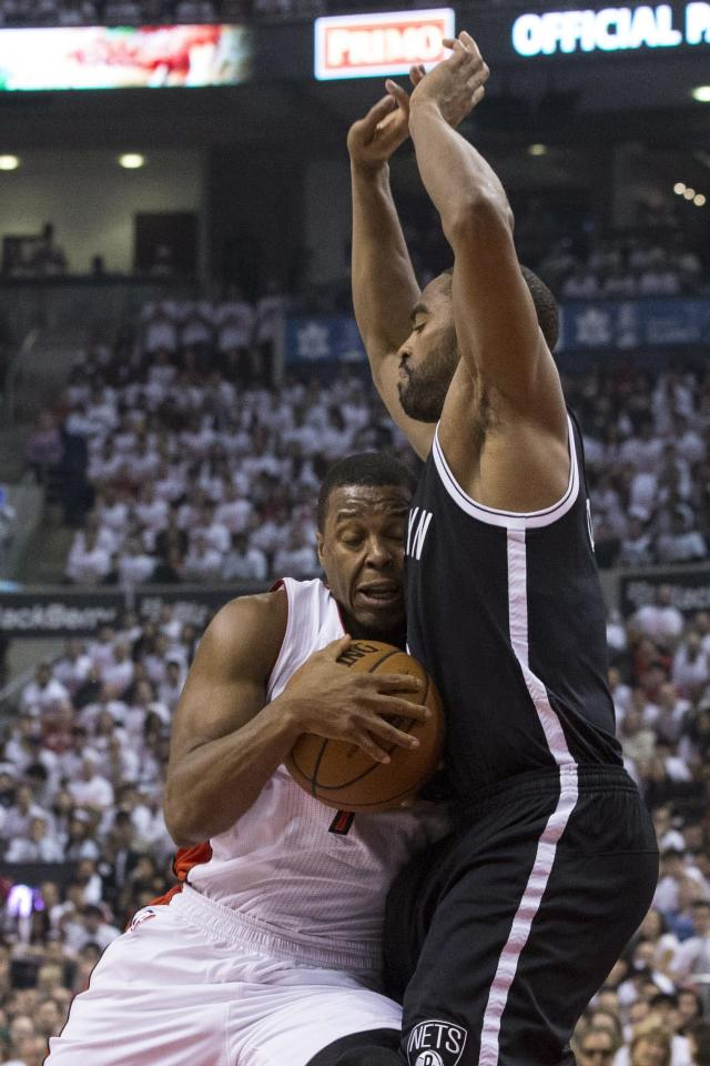 Toronto Raptors' Kyle Lowry, left, drives against Brooklyn Nets' Alan Anderson during the first half of Game 1 of an opening-round NBA basketball playoff series, in Toronto on Saturday, April 19, 2014. (AP Photo/The Canadian Press, Chris Young)