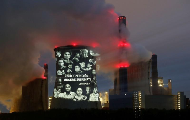 """Activists of the environmental organisation Greenpeace project a slogan that reads """"No Future in Fossil Fuels"""" on the cooling tower of RWE coal power plant, in Neurath"""