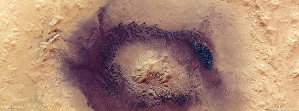 A new image from the European Space Agency's Mars Express orbiter reveals an odd, misshapen impact crater known as Moreux crater. While most craters appear roughly circular in shape, the outline of Moreux crater is shaped more like a fried egg. The crater's dark walls appear ridged and rippled, while dark brown and black dunes are smeared across the crater floor. The tall peak in its center is a pile of material that was ejected from the Martian terrain when the initial impact happened a few million years ago. Moreux crater's contorted appearance  developed over a long period of time, as erosion, wind and glacial activity shaped the planet's surface. This image was created using data collected by the High Resolution Stereo Camera on Mars Express, when the spacecraft flew over the area in October 2019.